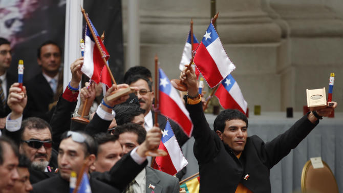 FILE - In this Oct. 25, 2010 file photo, rescued miners raise Chilean flags presented by Chile's President Sebastian Pinera, unseen, during a ceremony to honoring them at La Moneda presidential palace in Santiago, Chile. One of the myths surrounding the 33 miners who survived 69 days, 700 feet deep, and whose unprecedented and dramatic rescue was beamed to millions around the world, is that they are millionaires and do not need work. A year after the tragedy, nearly half are unemployed, one lives the fame that began to take shape at the bottom of the mine, many have chosen to give motivational talks to make a living and and four returned to work in the mines. (AP Photo/Roberto Candia, File)