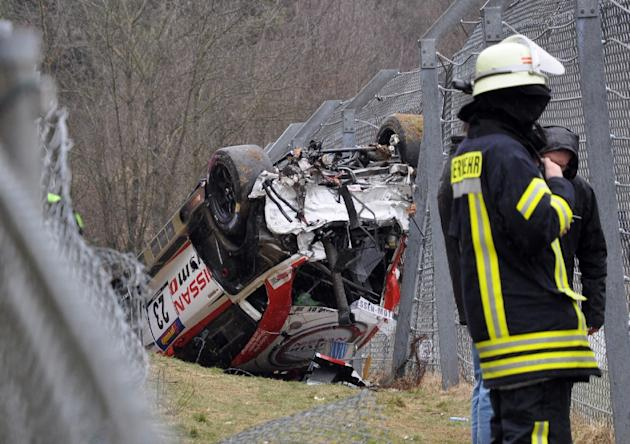 A member of the emergency services works at the scene where the Nissan of British driver Jann Mardenborough lays overturned in Nurburgring, Germany on March 28, 2015 (AFP Photo/Andreas Winkler)