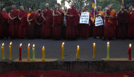 Tibetan exile monks stand during a candlelit vigil in New Delhi, India, to express solidarity with the plight of the Tibetan people in Tibet, Tuesday, Oct. 18, 2011.A Tibetan nun has set herself on fire in western China, the latest in a series of self-immolations among the region's Buddhist clergy, an advocacy group said Tuesday. (AP Photo/Manish Swarup)