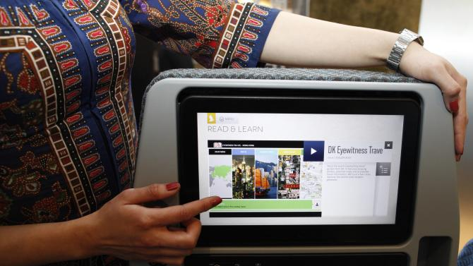 A Singapore Airlines Ltd stewardess poses with a new wider 11.1 inch monitor of the economy cabin during the launch of their new generation of cabin products in Singapore