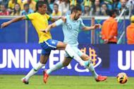 Karim Benzema (R) of France is challenged by Luis Gustavo of Brazil during a friendly between the sides at the Gremio stadium in Porto Alegre, Brazil on June 9, 2013. Real Madrid's French international Karim Benzema has undergone a surgical procedure in France to drain liquid from his right knee, the club said on its web site