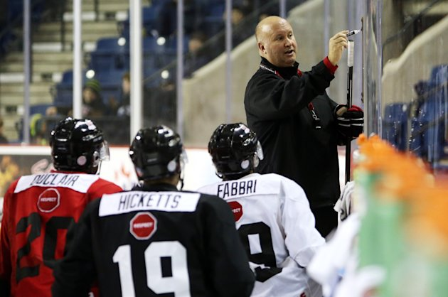 Coach Benoit Groulx draws on a white board during Team Canada practice. (Photo by Vaughn Ridley/Getty Images)