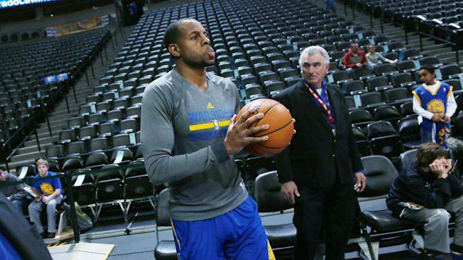 Golden State Warriors guard Andre Iguodala, foreground, steps onto the court of the Pepsi Center to warm up before facing the Denver Nuggets in an NBA basketball game in Denver, Monday, Dec. 23, 2013. Iguodala is making his first appearance in Denver since being dealt by the Nuggets to Golden State in the off-season