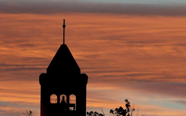 The sunsets over a church in the Australian capital Canberra venue for the Cricket World Cup Pool B match between South Africa and Ireland, in Australia, Tuesday, March 3, 2015. (AP Photo/Rob Griffith