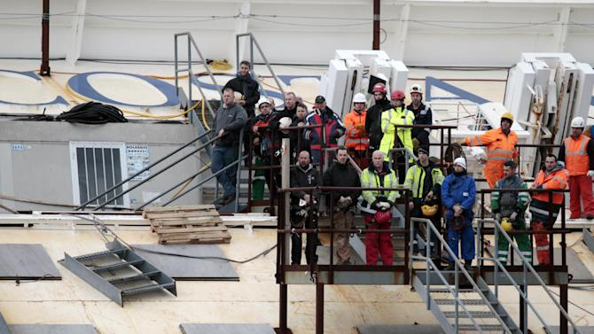 Workers observe a minute silence as they stand on the Costa Concordia cruise ship leaning on its side off the Tuscan Island Isola del Giglio, Italy, Sunday, Jan. 13, 2013. Survivors of the Costa Concordia shipwreck and relatives of the 32 people who died marked the first anniversary of the grounding Sunday. The first event of Sunday's daylong commemoration was the return to the sea of part of the massive rock that tore into the hull of the 112,000-ton ocean liner on Jan. 13, 2012 and remained embedded as the vessel capsized along with its 4,200 passengers and crew. (AP Photo/Gregorio Borgia)