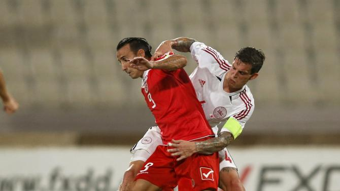 Malta's Mifsud and Denmark's Agger fight for the ball during their 2014 World Cup qualifying soccer match at the National Stadium in Ta' Qali, outside Valletta