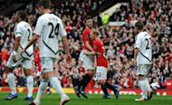 Manchester United's Michael Carrick (3rd R) congratulates goal-scorer Paul Scholes (2nd R) during their Premier League match against Swansea City on May 6. Scholes gave United a 28th-minute lead after turning in a shot from Carrick