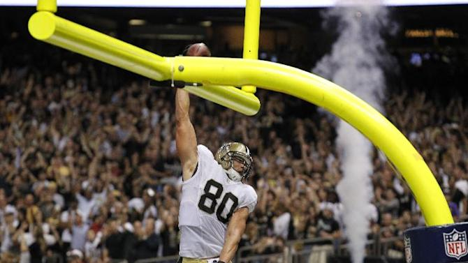 New Orleans Saints tight end Jimmy Graham (80) slam dunks over the goalpost after scoring on a touchdown reception in the second half of an NFL football game against the Arizona Cardinals in New Orleans, Sunday, Sept. 22, 2013