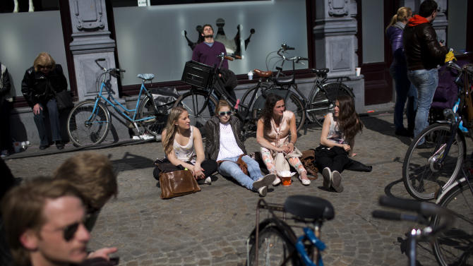 People sunbathe in Dam square in downtown Amsterdam, Netherlands Monday, April 29, 2013. Queen Beatrix has announced she will relinquish the crown on April 30, 2013, after 33 years of reign, leaving the monarchy to her son Crown Prince Willem-Alexander. (AP Photo/Emilio Morenatti)