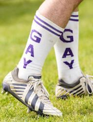 """Berlin Bruisers captain Colin Comfort wears socks reading """"Gay"""" on them during a training with Welsh rugby player Gareth Thomas on May 23, 2014 in Berlin"""