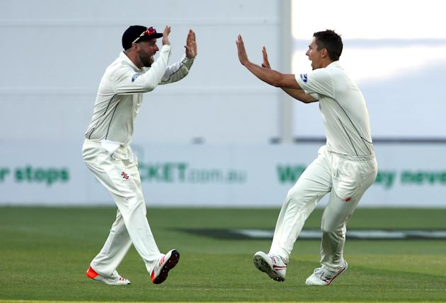 New Zealand's Trent Boult celebrates with team mate Mark Craig after he dismissed Australia's Adam Voges for 28 runs during the third day of the third cricket test match at the Adelaide Oval,