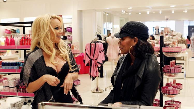 "Pamela Anderson poses as a lingerie salesperson on ""I Get That A Lot."""