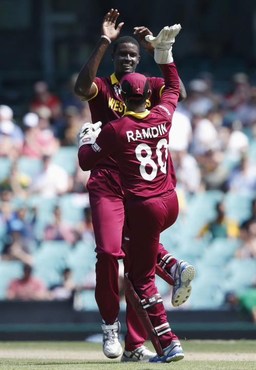 West Indies bowler Holder celebrates with wicketkeeper Ramdin after dismissing South Africa's de Kock for twelve runs during their Cricket World Cup match at the SCG