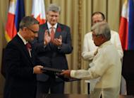 Philippine President Benigno Aquino (back R) and Canadian Prime Minister Stephen Harper (back L) applaud as Philippine National Defense Secretary Voltaire Gazmin (front R) and Ed Fast, Canadian Minister of International Trade, exchange documents after signing a deal Saturday to help Manila buy military equipment to defend its territory