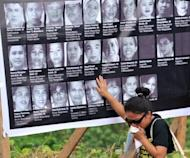 A relative of one of the 57 victims of the 2009 massacre cries as she touches the photos of the victims during a memorial service on the first annivesary of the massacre on the southern island of Mindanao