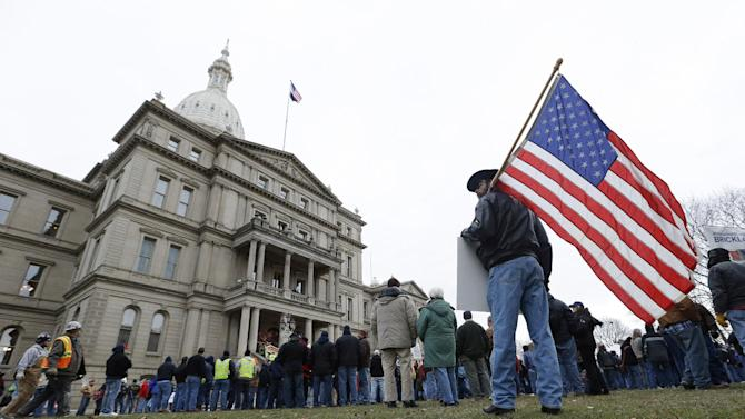 A protester holds an American flag at a rally on the State Capitol grounds in Lansing, Mich., Tuesday, Dec. 11, 2012. The crowd is protesting right-to-work legislation passed last week. Michigan could become the 24th state with a right-to-work law next week. Rules required a five-day wait before the House and Senate vote on each other's bills; lawmakers are scheduled to reconvene Tuesday and Gov. Snyder has pledged to sign the bills into law. (AP Photo/Paul Sancya)