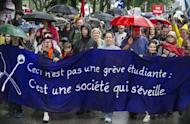 "Thousands of people took to the streets of Montreal braving driving rain to protest planned tuition hikes after talks between students and the Quebec government broke down. Banner reads ""This is not a student strike, it's a community awakening"""