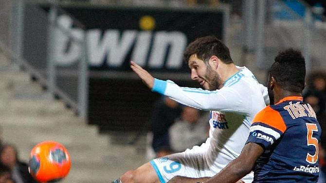 Marseille's French forward Andre-Pierre Gignac, left,  challenges for the ball with Montpellier's defender Siaka Tiene from Ivory Coast, during their League One soccer match, at the Velodrome Stadium, in Marseille, southern France, Friday, Nov. 29, 2013