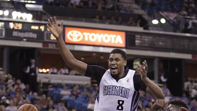 Sacramento Kings forward Rudy Gay, center, is stripped of the ball by Milwaukee Bucks forward Jeff Adrien, right, as Bucks guard Ramon Sessions, left, looks on during the fourth quarter of an NBA basketball game in Sacramento, Calif., Sunday, March 23, 2014.  The Kings won 124-107