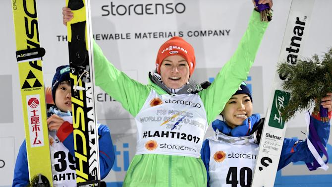 Second placed Yuki Ito of Japan, winner Carina Vogt of Germany and third placed Japan's Sara Takanashi celebrate on the podium after the ladies normal hill (HS100) ski jumping final in the FIS Nordic Ski World Championships in Lahti