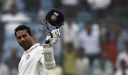 File photo of India's Tendulkar raising his cap in celebration after completing 15,000 runs in his test career during the third day of their first test cricket match against West Indies in New Delhi