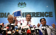 Malaysian acting Transport Minister Hishamuddin Hussein, center, shows maps of South Corridor and North Corridor of the search and rescue as director general of the Malaysian Department of Civil Aviation, Azharuddin Abdul Rahman, right, and Malaysian Deputy Foreign Minister Hamzah Zainudin during a press conference at a hotel next to the Kuala Lumpur International Airport, in Sepang, Malaysia, Monday, March 17, 2014. The search for the missing Malaysian jet pushed deep into the northern and southern hemispheres Monday as Australia took the lead in scouring the seas of the southern Indian Ocean and Kazakhstan - about 10,000 miles to the northwest - answered Malaysia's call for help in the unprecedented hunt. (AP Photo/Vincent Thian)