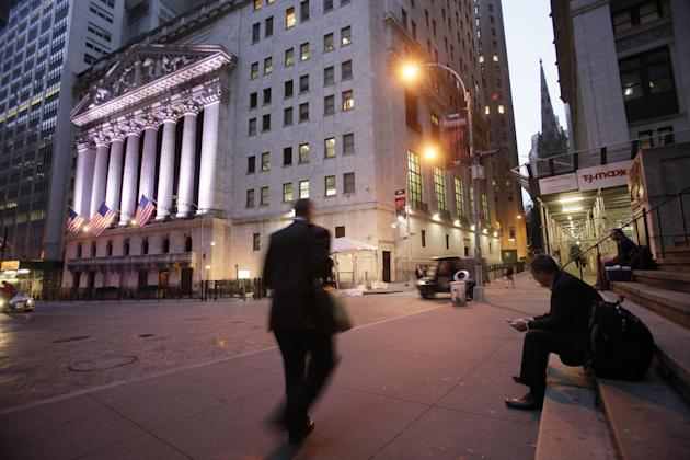 FILE - In this Oct. 8, 2014 file photo, a man walks to work on Wall Street, near the New York Stock Exchange, in New York. Global stocks were mixed on Friday, July 31, 2015, with China's stock mar