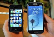 "An employee shows an Apple's iPhone 4s (L) and a Samsung's Galaxy S3 (R) at a mobile phone shop in Seoul on August 27, 2012. A jury in San Jose, California decided Friday that Samsung ""wilfully"" infringed six Apple patents for smartphones or tablet PCs"