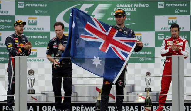 Mark Webber of Australia holds up the Australian flag in front of Sebastian Vettel of Germany, Christian Horner and Fernando Alonso of Spain on the podium after the Brazilian F1 Grand Prix at the Inte