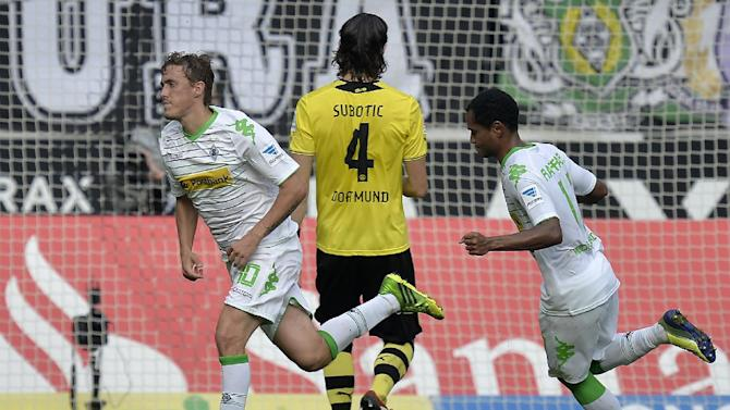 Moenchengladbach's two scorers Max Kruse, left, and Raffael, right, are passing Dortmund's Neven Subotic of Serbia, center, after scoring a penalty during the German first division Bundesliga soccer match between Borussia Moenchengladbach and Borussia Dortmund in Moenchengladbach, Germany, Saturday, Oct. 5, 2013. Moenchengladbach defeated Dortmund with 2-0