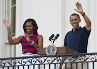 US President Barack Obama and First Lady Michelle Obama at an Independence Day celebration in Washington, DC on July 4. First Lady Michelle Obama will head the US delegation in London to watch the Olympic cauldron lit by a mystery personality in a £27 million extravaganza