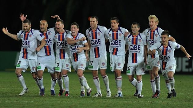 Perth Glory players celebrate after Jacob Burns scored his penalty to defeat the Central Coast Mariners during their Grand Final qualifier in Gosford on Saturday, April 14, 2012. (AAP AUSTRALIA USE ONLY)