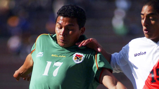 FILE - In this Oct. 9, 2004 file photo, Bolivia's Gatty Ribeiro, left, fights for the ball with Peru's Guillermo Sallas at a World Cup qualifying match in La Paz, Bolivia. Ribeiro, who retired from professional soccer, won the mayoral election in the town of Cobija, Bolivia on March 29, 2015. (AP Photo/Dado Galdieri, File)