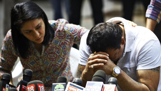 Indian Bollywood actor Sanjay Dutt, right, breaks down as his sister Priya Dutt tries to console him during a press conference at his residence in Mumbai, India, Thursday, March 28, 2013. Dutt says he has not sought pardon for a 1993 weapons conviction and will serve his prison sentence as ordered by India's Supreme Court. Dutt broke his silence a week after the court sentenced him to five years in prison for illegal possession of weapons supplied by Mumbai crime bosses linked to a 1993 terror attack that killed 257 people.(AP Photo/Rafiq Maqbool)