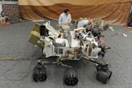"Jet Propulsion Laboratory (JPL) engineers examine a full size engineered model of the Mars rover Curiosity, on August 2. About 36 hours after the US space agency's landed its $2.5 billion rover on Mars, NASA released Tuesday what it called a ""crime scene"" aerial shot of where the parachute, heat shield and rover came down"