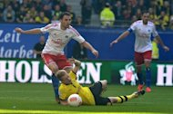 Hamburg's midfielder Milan Badelj (L) and Dortmund's striker Marco Reus (C) fight for the ball during their German Bundesliga football match in Hamburg, northern Germany. Dortmund's 31-match unbeaten run came to an end in a shock 3-2 loss at struggling Hamburg, who registered their first league win of the season