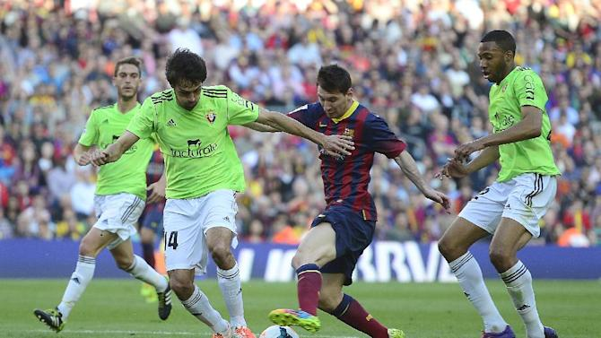 FC Barcelona's Lionel Messi, from Argentina, center, duels for the ball against Osasuna's Alejandro Arribas during a Spanish La Liga soccer match at the Camp Nou stadium in Barcelona, Spain, Sunday, March 16, 2014
