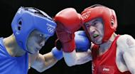 Paddy Barnes of Ireland (in red) defends against Devendro Singh Laishram of India (in blue) during the Light Flyweight boxing quarterfinals of the 2012 London Olympic Games at the ExCel Arena in London. Barnes advanced to the semi-finals with a 23-18 points decision