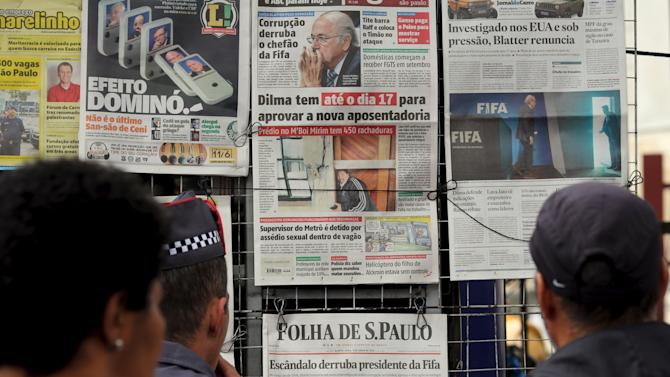 People read the local newspaper front pages showing pictures of FIFA's Joseph Blatter in Sao Paulo