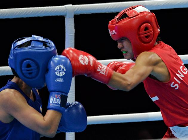 Leona Hui of Singapore (right) fights against Jose Gabuco of the Philippines during their women's light flyweight semifinal boxing bout at the 28th Southeast Asian Games (SEA Games) in Singapore o