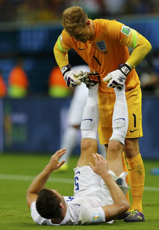 England's Joe Hart helps England's Cahill stretch during World Cup soccer match between England and Italy at Amazonia arena