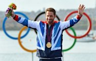 Britain's Ben Ainslie acknowledges the applause on the podium after receiving the gold medal in the Finn sailing class at the London 2012 Olympic Games, in Weymouth on August 5, 2012. Ainslie said on Tuesday that he may yet carry on to the 2016 Rio Olympics after all