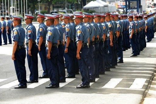 Philippine police officers stand at attention during a gathering at the Philippine National Police headquarters in suburban Manila in 2011. A Philippine policeman has been detained in connection with the kidnapping and murder of a woman after he was caught on camera driving the victim's vehicle, an official said on Tuesday