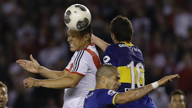 River Plate's Teofilo Gutierrez, left, fights for the ball with Boca Juniors' Gonzalo Escalante, right, and Daniel Diaz during an Argentina's league soccer match in Buenos Aires, Argentina, Sunday, Oct. 6, 2013