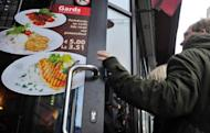 A man enters a restaurant in Riga, Latvia on December 27, 2013, where prices of the dishes are displayed in Lats and Euros