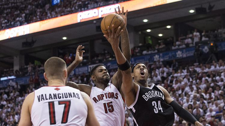 Brooklyn Nets' Paul Pierce, right, is fouled by Toronto Raptors' Amir Johnson, center, as Raptors' Jonas Valanciunas watches during the second half of Game 1 of an opening-round NBA basketball playoff series, in Toronto on Saturday, April 19, 2014. The Nets won 94-87