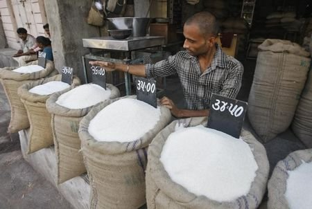 A vendor arranges a price tag over a sack filled with sugar at a wholesale vegetable market in Ahmedabad September 11, 2013. REUTERS/Amit Dave/Files