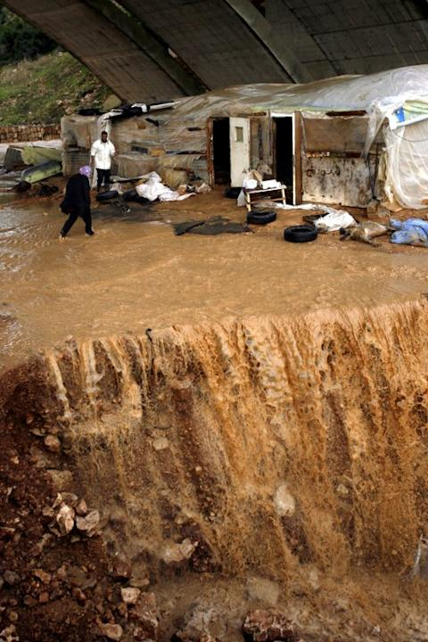 A woman crosses despite of the water that overflows after heavy rains and big wind on January 7, 2013 in the Lebanese southern city of Jadra. Stormy weather, including high winds and heavy rainfall, l