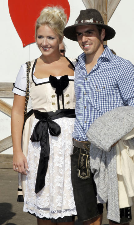 Philipp Lahm, right, of Bayern Muenchen and his wife Claudia arrive a beer tent during the 178th Oktoberfest beer festival in Munich, southern Germany, on Sunday, Oct. 2 , 2011. (AP Photo/Matthias Sch