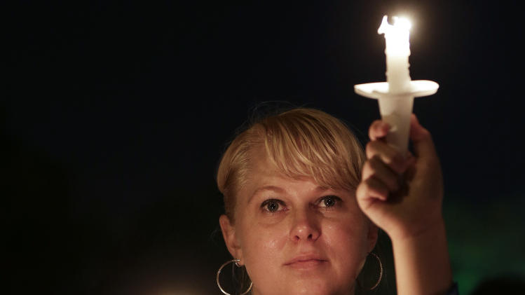 Holly Tucker of Nashville, Tenn., attends a candlelight vigil at Graceland, Elvis Presley's Memphis home, on Wednesday, Aug. 15, 2012. Fans from around the world are at Graceland to commemorate the 35th anniversary of Presley's death. (AP Photo/Mark Humphrey)